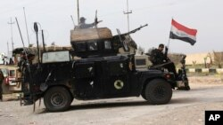 FILE - Iraqi security forces prepare to attack Islamic State extremists at Camp Speicher, the front line in Tikrit, 80 miles (130 kilometers) north of Baghdad, March 12, 2015.