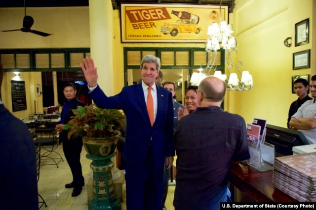 U.S. Secretary of State John Kerry waves to tourists after he entered the famed Foreign Correspondents Club in Phnom Pehn, Cambodia, Jan. 25, 2016.
