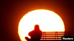 FILE - A man rests during sunset after a long and hot summer day at Dubai's popular Jumeirah beach.