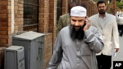 FILE - In this April 11, 2007 file photo, Egyptian cleric Osama Hassan Mustafa Nasr, also known as Abu Omar, who was allegedly kidnapped by CIA agents in an Italian city and taken to Egypt, talks on his mobile phone as he walks in a Cairo street.