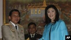 ນາຍພົນ Min Aung Hlaing (ຊ້າຍ) ຜູ້ບັນຊາການສູງສຸດກອງທັບມຽນມາ ຈັບມືກັບທ່ານນາງຍິ່ງລັກ ຊິນນະ ວັດ ນາຍົກລັດຖະມົນຕີໄທ ທີ່ທຳນຽບລັດຖະບານ ຢູ່ບາງກອກ (10 ມັງກອນ 2012)