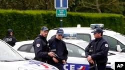 Des policiers français bloquent la route menant à une scène de crime le lendemain de l'attaque au couteau de lundi soir, à l'ouest de Paris, France, le mardi 14 juin 2016. (AP Photo / Thibault Camus)