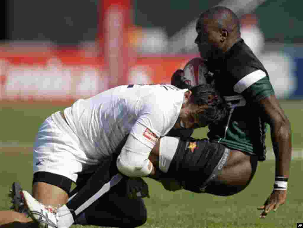 England's Chris Cracknell, left, tackles Fourtune Chipendu from Zimbabwe during the first day of the Dubai Rugby Sevens, Friday, Dec. 2, 2011 in Dubai, United Arab Emirates. (AP Photo/Kamran Jebreili)