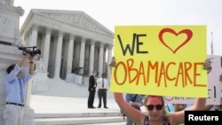 Supporters of the Affordable Care Act gather in front of the Supreme Court before the court's announcement of the legality of the law in Washington on June 28