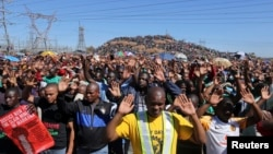 Miners gesture as they pray during the one-year anniversary commemorations to mark the killings of 34 striking platinum miners fatally shot by police outside the Lonmin's Marikana platinum mine in Rustenburg, 100 kilometers northwest of Johannesburg, Aug.