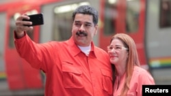 Venezuela's President Nicolas Maduro takes a selfie next to his wife, Cilia Flores, as they arrive for a rally with workers of transport sector in Caracas, Venezuela, Jan. 24, 2018.