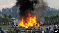 """Warga Nepal berkerumun mengelilingi kepingan pesawat """"SIta Air"""" yang terbakar dan jatuh dekat Katmandu, Nepal (28/9)."""