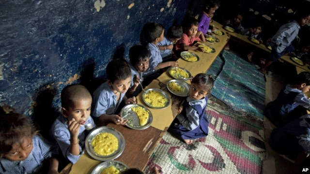 Children eat a meal at a school in a shanty neighborhood of New Delhi, India, Sept. 13, 2012.