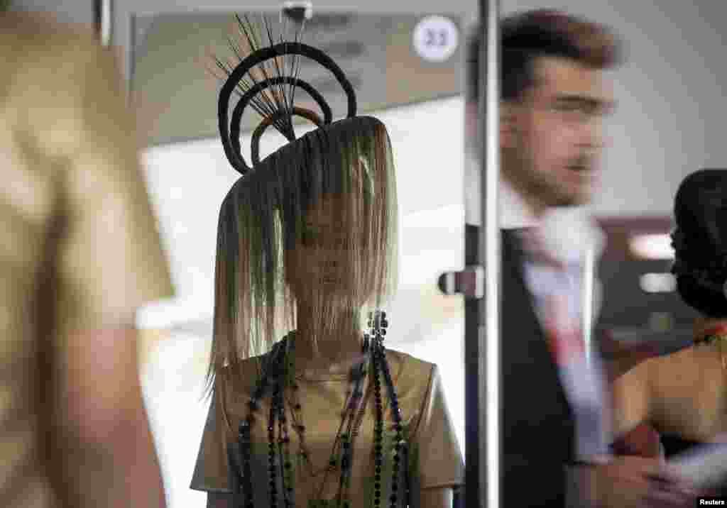 A model is reflected in a mirror as she presents a hairstyle during a national championship on hairdressing, nail esthetics, make-up and body art in Almaty, Kazakhstan.