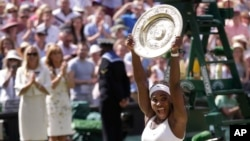 FILE - Serena Williams of the United States reacts as she holds up the trophy after winning the women's singles final against Garbine Muguruza of Spain, at the All England Lawn Tennis Championships in Wimbledon, London, July 11, 2015.