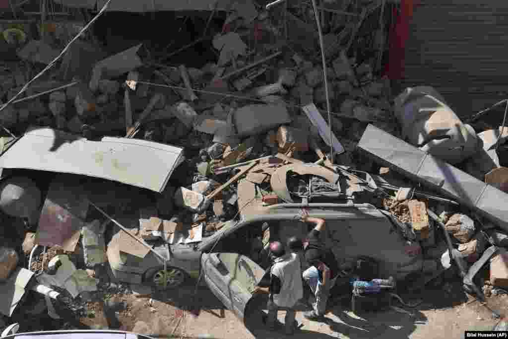 Люди оглядають свою автівку, яку була пошкоджена внаслідок вибуху у порту Бейрута. 5 серпня.