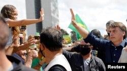 Presiden Brazil Jair Bolsonaro menyapa para pendukungnya di depan Istana Planalto di tengah pandemi virus corona (Covid-19), 24 Mei 2020. (Foto: Reuters)