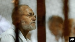 FILE - Leader of Egypt's Muslim Brotherhood Mohamed Badie sits inside a defendant's cage during his trial in Cairo, Egypt, April 30, 2014.