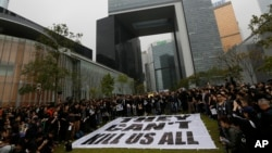 """Các nhà báo và người ủng hộ đứng cạnh một biểu ngữ lớn với hàng chữ """"Họ không thể giết tất cả chúng ta"""" bên ngoài trụ sở chính phủ ở Hồng Kông, ngày 2/3/2014."""