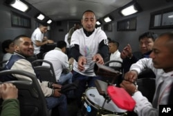In this July 19, 2019 photo, inmate Martin Reano is passed an instrument inside an armored bus that will transport him and fellow inmates to the Peruvian capital for a classical music session at the national theater.