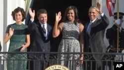 De izquierda a derecha, Agnese Landini esposa del primer ministro, Matteo Renzi, Michelle Obama, presidente Barack Obama saludan desde el balcón Truman de la Casa Blanca.