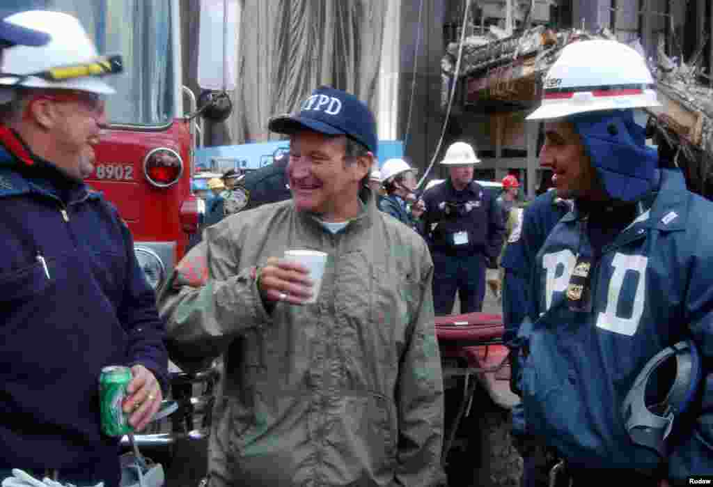 Actor and comedian Robin Williams (center) shares a laugh with rescue workers near the site of the World Trade Center collapse in lower Manhattan, Oct. 17, 2001. Williams spent time with rescue workers as well as surprising their wives with phone calls.