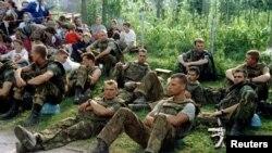 Pripadnici nizozemskog bataljona UN-a odmaraju se sjedeći pored izbjeglica iz Srebrenice koje čekaju na prijevoz iz Potočara.