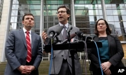 Attorney General Bob Ferguson, center, stands with Solicitor General Noah Purcell, left, and Civil Rights Unit Chief Colleen Melody as he speaks with media members on the steps of the federal courthouse after an immigration hearing there, March 15, 2017,