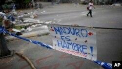 Un cartel en rechazo al presidente Nicolás Maduro es desplegado en una calle de Caracas, Venezuela, el miércoles, 26 de julio de 2017, como parte de una barricada en el paro de 48 horas convocado por la oposición.