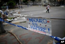 "A sign that reads in Spanish: ""Maduro is hunger!"" forms part of a barricade made by demonstrators during a 48-hour general strike beginning July 26, 2017. In the capital, Caracas, many residents stayed home in observance of the strike."