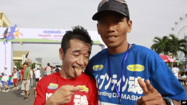 Japanese entertainer Neko Hiroshi, left, poses with Cambodian winner Em Buntin after a half marathon Saturday, June 18, 2011 in Phnom Penh, Cambodia. The Japanese finished second. More than 1,000 Cambodians and foreigners took part in the running, celebra