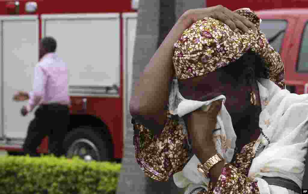 An unidentified victim weeps after a bomb blast that ripped through the United Nations offices in the Nigerian capital of Abuja August 26, 2011. The blast happened after a car rammed into the building, and witnesses said they had seen a number of dead bod