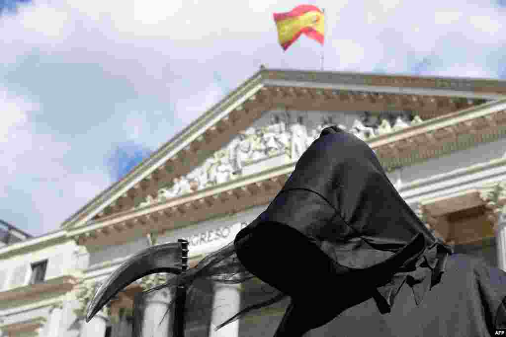 A protester dressed as Death demonstrates against a law legalizing euthanasia, as Parliament gives final approval to bill decriminalizing euthanasia and physician-assisted suicide, in Madrid.
