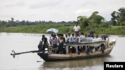 FILE - Rohingya Muslims travel on a boat along a river in Buthidaung township, Myanmar, June 7, 2015. A boat carrying more than 60 people capsized in rough waters off of Sittwe in Myanmar's Rakhine state Tuesday.