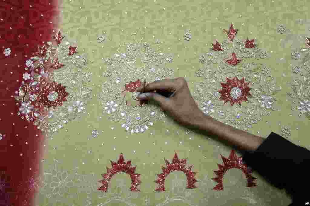 A Bangladeshi man works at an embroidery factory before Eid al-Fitr celebrations in Dhaka, Bangladesh, July 30, 2013.