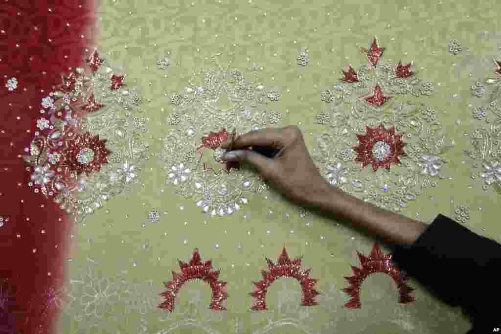 A Bangladeshi man works at an embroidery factory before Eid al-Fitr celebrations in Dhaka, Bangladesh, July 30, 2013.