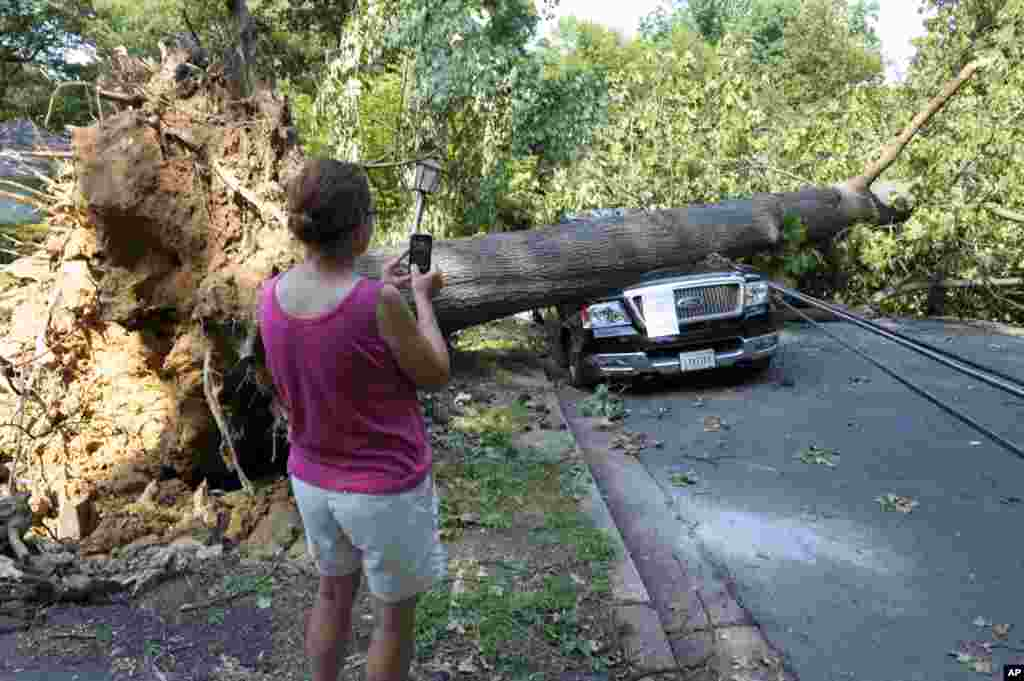 A woman takes photograph of Mike Wolfe's pick-up truck as it lies under a fallen tree in front of his house after a severe storm in Falls Church, Va., June 30, 2012.