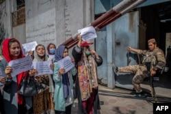 Tentara Taliban menyaksikan perempuan Afghanistan yang melakukan demonstrasi menuntut hak yang lebih baik bagi perempuan di depan bekas Kementerian Urusan Perempuan di Kabul pada 19 September 2021. (Foto: AFP)