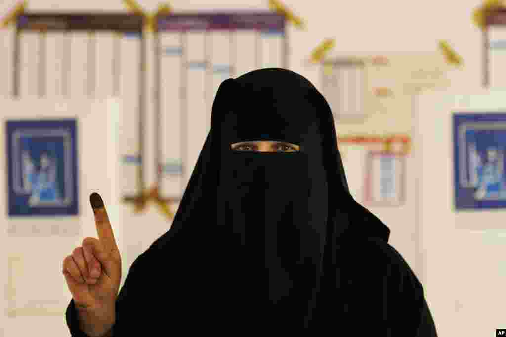An Iraqi woman displays her ink-stained finger at a polling center during the country's provincial elections in Fallujah, June 20, 2013.