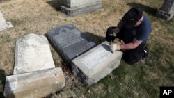 A Trump supporter named Bob, who declined to give his last name, volunteers his time and prepares the base of a damaged headstone, Feb. 28, 2017, in Philadelphia. Scores of volunteers are expected to help in an organized effort to clean up and restore the Jewish cemetery where vandals damaged hundreds of headstones.