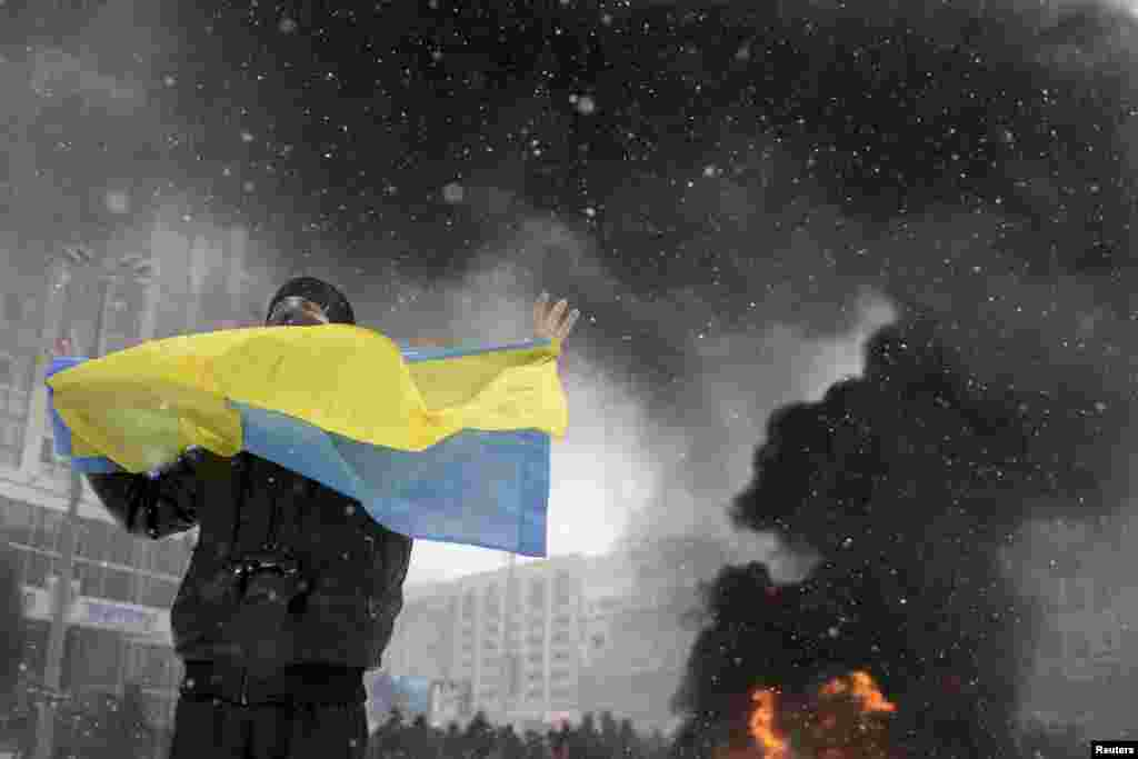 A man holds a Ukrainian flag as smoke rises in the background during clashes between police and pro-European protesters in Kyiv, Jan. 22, 2014.