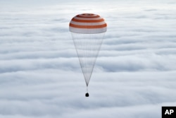 Russia's Soyuz TMA-18M space capsule carrying the International Space Station (ISS) crew members prepares to land in a remote area outside the town of Dzhezkazgan, Kazakhstan, Wednesday, March 2, 2016.