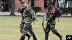 A Colombian soldier, left front, escorts rebels of the National Liberation Army, ELN, who gave themselves up at a military base in Cali, July 16, 2013.
