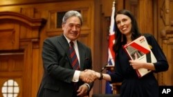 New Zealand First leader Winston Peters, left, and Prime Minister-designate Jacinda Ardern shake hands after signing a coalition agreement on Tuesday, Oct. 24, 2017, in Wellington. New Zealand.