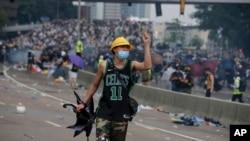 一名抗议香港逃犯条例修订的香港示威者向与抗议者发生冲突的防暴警察做手势。(2019年6月12日)