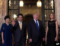 FILE - President Donald Trump and first lady Melania Trump stop to pose for a photo with Japanese Prime Minister Shinzo Abe, second from left, and his wife Akie Abe, left, before they have dinner at Mar-a-Lago in Palm Beach, Fla., Feb. 2017.
