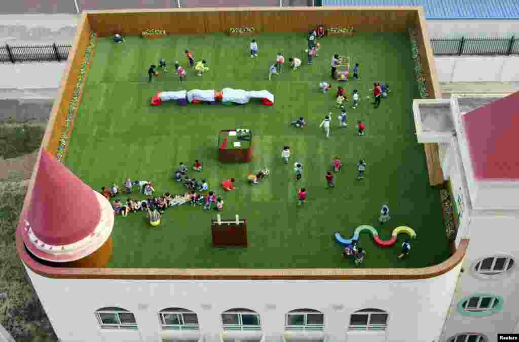Teachers and students exercise on the playground located on the roof of a kindergarten building in Xi'an, Shaanxi province, China, Oct. 20, 2015.