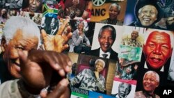 A well-wisher uses his phone to take a picture of a banner of photos of Nelson Mandela, outside the Mediclinic Heart Hospital where former South African President Nelson Mandela is being treated in Pretoria, South Africa Thursday, July 18, 2013. South Afr