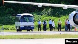 Người xin tị nạn được chuyển từ một máy bay lên xe buýt trên đảo Nauru ở Nam Thái Bình Dương. Dựa trên những chính sách cứng rắn, Australia chuyển những thuyền nhân tới các trại tạm giam tại Papua New Guinea và đảo quốc tí hon Nauru.