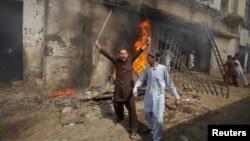 """Un manifestante grita consignas antiestadounidenses frente a un cine incendiándose en el """"día de amor"""" a Mahoma en Peshawar."""