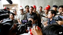 Cambodian Prime Minister Hun Sen, center, gives a press conference during his tour to an under construction bridge at Stung Mean Chey commune, in Phnom Penh, file photo.
