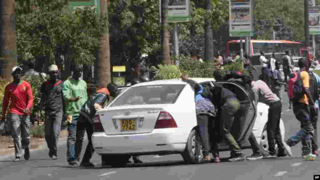 University students harass a motorist during a demonstration in Nairobi,, Kenya, Tuesday, Sept, 22, 2015.