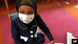 In this, May 2, 2017 photo, Amira Hassan plays in the waiting room at the specialty clinic at Children's Minnesota in Minneapolis. Hassan went to the hospital's clinic for a routine wellness check, but had to wear a mask to protect her from measles after
