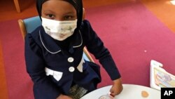 In this, May 2, 2017 photo, Amira Hassan plays in the waiting room at the specialty clinic at Children's Minnesota in Minneapolis. Hassan went to the hospital's clinic for a routine wellness check, but had to wear a mask to protect her from measles after an outbreak has sickened more than 30 children in Minnesota.