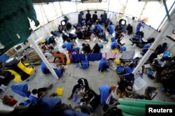 FILE - Migrants are seen on board the MV Aquarius, in the Mediterranean Sea, between Malta and Linosa, Aug. 14, 2018.